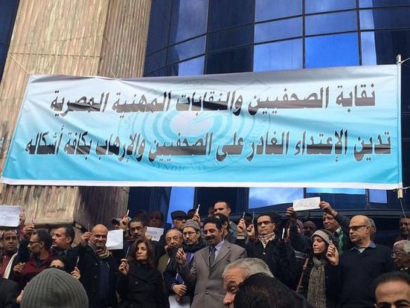 Members of the Egyptian journalist syndicate raise pens at a Charlie Hebdo gathering in Cairo